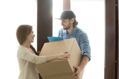 Delivery service concept, woman receiving box from courier at ho. Delivery service concept, women receiving cardboard box from men at home standing in hallway Royalty Free Stock Image