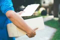 Delivery service courier in front of the house. Delivery service courier standing in front of the house with boxes and clipboard in hands Stock Photo
