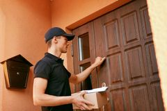 Delivery Service. Courier With Package Near Clients Door. Man Delivering Box To Home. High Resolution royalty free stock image