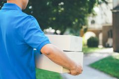 Delivery service courier standing in front of the house with box. Es and clipboard in hands royalty free stock photos