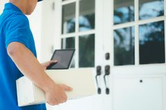 Delivery service courier in front of the house. Delivery service courier standing in front of the house with boxes and tablet in hands Stock Photo