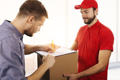 Delivery service - man signing delivery receipt of box. Delivery service - men signing delivery receipt of box at office Stock Image