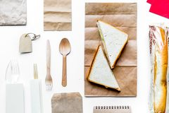 Delivery set with paper bags and sandwich on white background to. Delivery service set with paper bags and sandwich on white desk background top view royalty free stock images