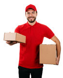 Delivery service - young smiling courier holding boxes on white Stock Photography
