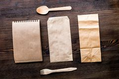 Delivery set with paper bags and flatware on wooden background t. Delivery service set with paper bags and flatware on wooden desk background top view stock image