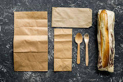 Delivery set with paper bags and sandwich on gray background top view Stock Images