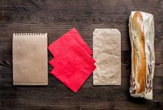 Delivery set with paper bags and sandwich top view mock up. Delivery service set with paper bags and sandwich on wooden desk background top view mock up stock image