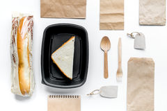 Delivery set with paper bags and sandwich top view space for text. Delivery service set with paper bags and sandwich on white desk background top view space for stock photo