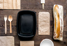 Delivery set with paper bags and sandwich top view space for text. Delivery service set with paper bags and sandwich on wooden desk background top view space for royalty free stock photos
