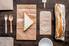 Delivery set with paper bags and sandwich top view space for text. Delivery service set with paper bags and sandwich on wooden desk background top view space for royalty free stock photography