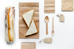 Delivery set with paper bags and sandwich on white background top view mockup. Delivery service set with paper bags and sandwich on white desk background top stock images