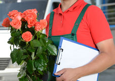 Delivery. Smiling young male delivery courier man in front of cargo van delivering flowers Royalty Free Stock Image