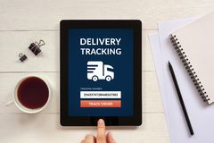 Delivery tracking concept on tablet screen with office objects. On white wooden table. All screen content is designed by me. Flat lay Royalty Free Stock Photography