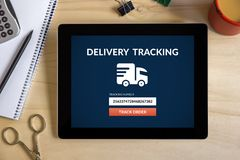 Delivery tracking concept on tablet screen with office objects. On wooden desk. All screen content is designed by me. Top view Royalty Free Stock Photo
