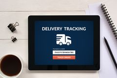 Delivery tracking concept on tablet screen with office objects. On white wooden table. All screen content is designed by me. Flat lay Stock Photo