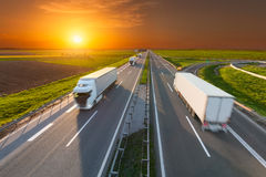 Delivery transport trucks on the empty highway at sunset. Many white trucks driving towards the sun. Fast blurred motion drive on the freeway at beautiful sunset Stock Images