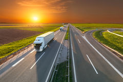 Delivery transport trucks on the empty highway at sunset. Three new white trucks driving towards the sun. Fast blurred motion drive on the freeway at beautiful Royalty Free Stock Photography