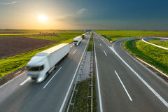 Delivery transport trucks on the highway at idyllic morning. Many new modern trucks in a row driving towards the sun at idyllic sunny day. Fast blurred motion Royalty Free Stock Photos