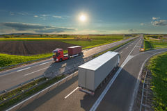 Delivery transport trucks on the highway at idyllic morning. Two new modern trucks driving towards the sun at idyllic sunny day. Fast blurred motion drive on the Royalty Free Stock Photos