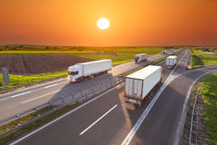 Delivery transport trucks on the highway at sunset. Many white trucks driving towards the sun. Fast blurred motion driving on the freeway at beautiful spring Stock Image
