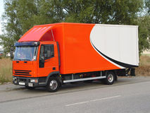 Delivery Truck. This is a picture of an orange and white, European delivery truck ready to deliver its goods Stock Images