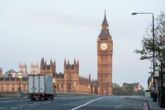A delivery truck crosses Westminster Bridge at dawn in London, UK