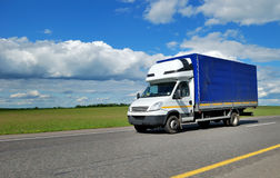 Delivery truck with white cabin and blue trailer
