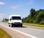 Delivery van. White van in a country road with some trees and a great blue sky above royalty free stock image