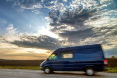 Delivery van on a country road. Asphalt road, journey to the Sunset Stock Image