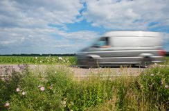 Delivery van driving with high speed along the country road royalty free stock image