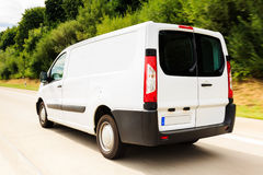 Delivery Van on the Highway. A white delivery van on a highway, motion blur. driver is model-released Royalty Free Stock Image