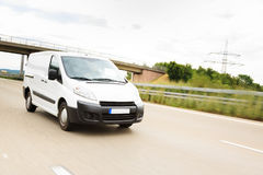 Delivery Van On Highway. A white delivery van on a highway, motion blur. driver is model-released Stock Images