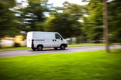 Delivery van moves on road. White delivery van speeding on road with blurred countryside panorama in background Royalty Free Stock Images