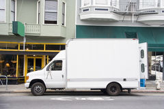 Delivery Van. White delivery van with open rear door parked next to urban businesses. Nobody. Horizontal Royalty Free Stock Photo