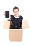 Delivery - woman in cardboard box holding mobile phone with blan Stock Photography