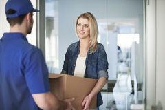 Delivery. Woman getting a parcel from delivery man Stock Photography