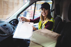 Delivery woman holding clipboard to camera Stock Photo