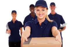 Delivery woman parcel. Friendly young delivery women presenting parcel with colleagues royalty free stock photo