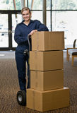 Delivery woman posing with stack of boxes Royalty Free Stock Photography