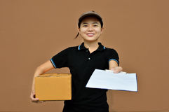 Delivery woman in  service with cardboard boxes and clipboard Stock Images