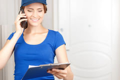 Delivery woman talking on mobile phone Royalty Free Stock Photography