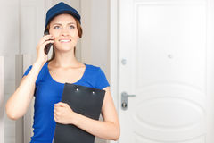 Delivery woman talking on mobile phone Stock Image