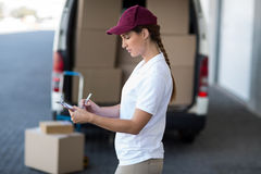 Delivery woman writing on clipboard while standing next to van Royalty Free Stock Photos