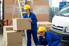 Delivery workers unloading cardboard boxes from pallet jack Stock Image