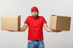 Delivery young man in red uniform holding two empty cardboard boxes isolated on white background. Copy space for. Advertisement royalty free stock photos