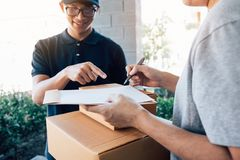 Delivery young man standing at the door of home and carrying parcels for young male to signing royalty free stock images