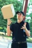 Deliveryman που χάνει ένα κιβώτιο δεμάτων, στη βιασύνη στοκ φωτογραφία