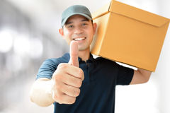 Deliveryman carrying a box, giving thumbs up royalty free stock photo