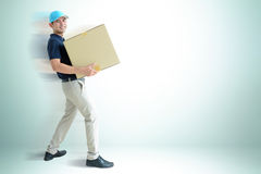 Deliveryman carrying a cardboard box Stock Photography