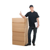 Deliveryman. Cheerful young deliveryman standing near the stack Stock Photos